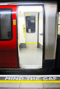 "Subway car open door, with ""MIND THE GAP"" on the platform edge."